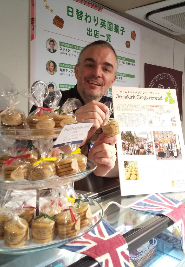 A picture of Paul Evans in his Japanese cafe, with his promotional poster, and small packets of traditional gingerbread biscuits. There is a Japanese billboard behind him, and Union flags in the foreground.